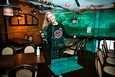 Ravintola Hookissa valmistaudutaan avaamaan ovet kesäkuussa. Tarjoilija Rebecca Vuorio kantaa pleksilasia, joka tulee pöytien väliin.
