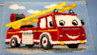 Kirsti Vallin paloauto edustaa neulalla tehtyä modernimpaa miniryijyä lapsenlapselle.