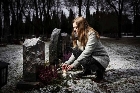 Veikon hautakivellä istuu lintu. Äiti Anna Elina Isoaro sytyttää lapselleen kynttilän Lamminpään hautausmaalla.