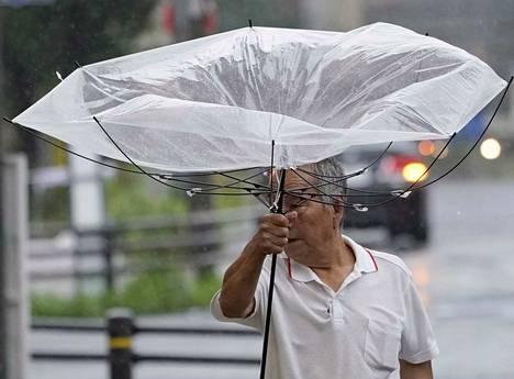 Kuvassa sateenvarjonsa kanssa kovassa tuulessa kamppaileva jalankulkija Tokiossa 9.9.2019.