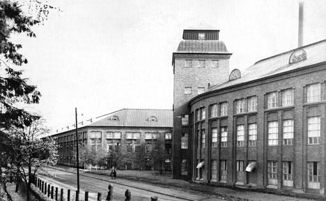 Suomen Gummitehtaan julkisivu kuvattuna vuosina 1910-1950. Tie tehtaan ohi kulki tehtaan seinän vierustaa.