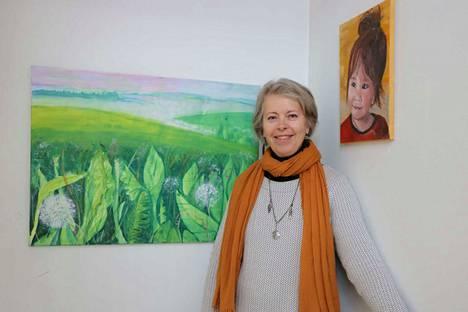 Ritva Utukka asuu Jyväskylässä, mutta käy Mänttä-Vilppulassa vierailemassa. Taustalla kaksi hänen työtään KMV-lehden porrasnäyttelystä.