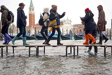 Ihmiset väistivät vettä kävelemällä penkkien päällä Venetsiassa.