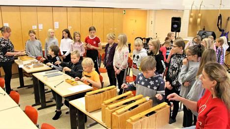Leena Ahti vasemmalla ja Airi Niemelä edessä oikealla ohjaavat Kivelän koulun musiikkiryhmän yhteisharjoitusta kirkkokonserttia varten.