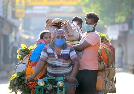 Intialaiset matkustavat mopon kyydissä Kolkatassa maanantaina rikkoen näin ulkonaliikkumiskieltoa.