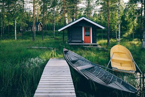 Traditional wooden hut. Finnish sauna on the lake and pier with fishing boats. Summer landscape