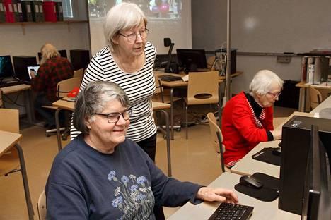 Anja Luusalo neuvoo Pirkko Huillaa kirjautumaan tietokoneelle. Vieressä harjoittelee Aino Asmala.