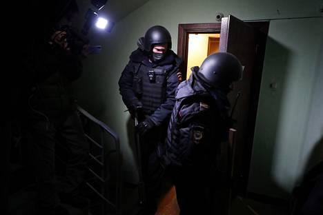 Poliisit lähdössä keskiviikkona Aleksei Navalnyin kodista Moskovassa kotietsinnän jälkeen.