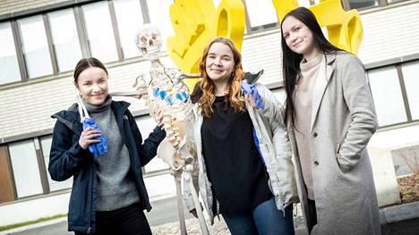 Henna Silvola, Saara Kenola ja Ella Saloharju ulkoiluttavat oppimateriaalia eli Armas-luurankoa kampuksen pihamaalla.