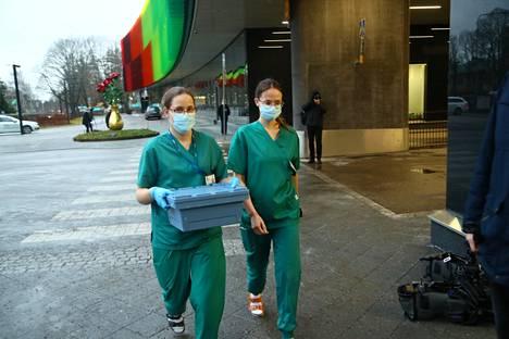Husin hoitajat kantavat koronarokotteita pahvilaatikossa rokotuspaikalle.