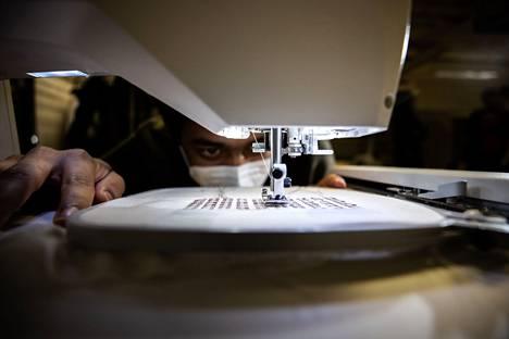 Kun Tampereen yliopiston Hervannan kampuksen laboratoriossa kehitetään älytekstiilejä, ompelukoneessa käytetään sähköä johtavaa lankaa. Adnan Mehmood ompelee RFID-siruja puuvillakankaaseen.