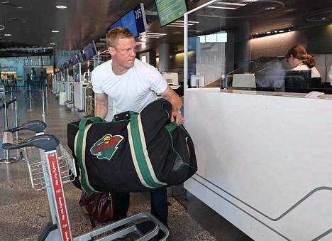 Mikko Koivu heittämässä Minnesotan pelikassia lentokentän laukkuhihnalle.