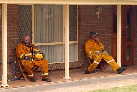 Uupuneet palomiehet viettävät lepohetkeä Adelaidessa.