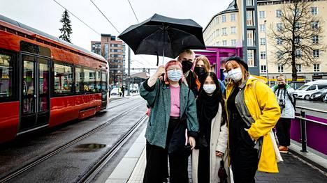 """Tampereen ratikan ensimmäiset matkustajat pääsivät kyytiin Pyynikintorin pysäkiltä. Mimmi Ahonen (vasemmalla edessä), Ville Vuorikoski, Pinja Puurunen, Rowena Hurme (edessä keskellä) ja Lotta Rahkonen odottivat ratikan saapumista. Ystävykset kertoivat halunneensa päästä testaamaan ratikkaa ensimmäisten joukossa """"rakkaudesta Tampereeseen""""."""