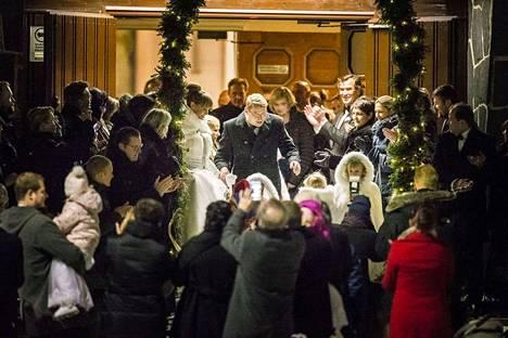 Hääpari valkoisiin puettuine lapsineen lähtivät kirkosta pororeen vetäminä.