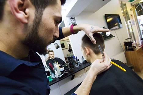 Veitsellä tukan kimppuun! Turkkilainen parturi Friendsin perustaja Samin Ali Salam käsittelee Johannes Thirolfin frisööriä.