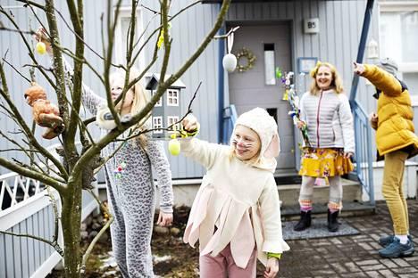 Opettaja Minna Rintala (takana) järjestää lapsilleen munanmetsästyksen perheen omassa pihapiirissä.