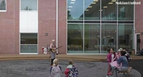 Myllyhaan koulussa vietetään uuden koulurakennuksen vihkijäisiä elävää musiikkia kuunnellen.