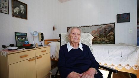 Eeva Pirinen kotonaan Valkeakosken Apianpirtissä. Seinällä on vihkikuva hänestä ja hänen miehestään Einarista.