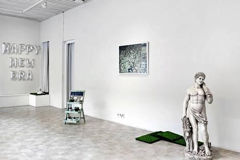 Juha Allan Ekholm: Happy New Era, ilmapallokirjaimet julistavat uutta aikakautta kasvitieteilijä Theofrastoksen muistomerkille ja Herakles-hahmolle.