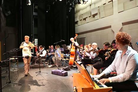 Arto Järvelä (vasemmalla) saa muusikot innostumaan, kun Bedstefar-kappaletta opetellaan korvakuulolta. Sanna Eronen (oikealla) hakee sointuja harmonillaan.