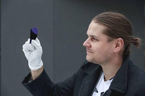 Tampereen yliopiston tutkijatohtorin Erkka Frankbergin kädessä olevan piikiekon pinnassa oleva violettia väriä heijastava ohutkalvo on ainutlaatuista terästäkin lujempaa lasia, jonka kaltaista ei ole aikaisemmin kukaan onnistunut tekemään.