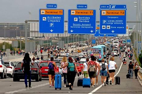 Ihmiset kävelivät maanantaina Barcelonan lentokentälle.