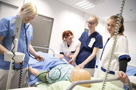 Lähihoitajaksi Winnovassa opiskelevat Johanna Stenroos (vasemmalla), Kamilla Lehtonen, Henna-Sofia Pohjola ja Nella Agge harjoittelevat hoitotoimia nuken kanssa.