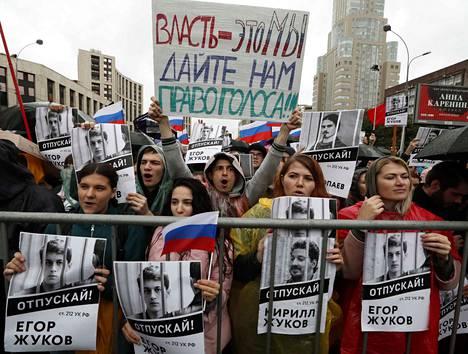 Venäjän opposition kannattajat pitelevät pidätettyjen paikallisvaaliehdokkaiden kuvia mielenosoituksessa Moskovan keskustassa.