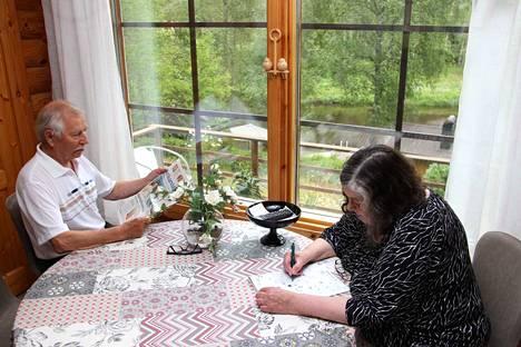 Pentti ja Arja Pirisen mökki sijaitsee korkealla jokitöyräällä. Näkymä tuvan ikkunasta on upea.