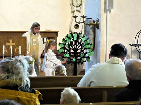 Viisivuotias Milja Aalto avusti pastori Annukka Lindbergiä muun muassa ripustamalla uusien kastettujen nimet kirkon kastepuuhun.