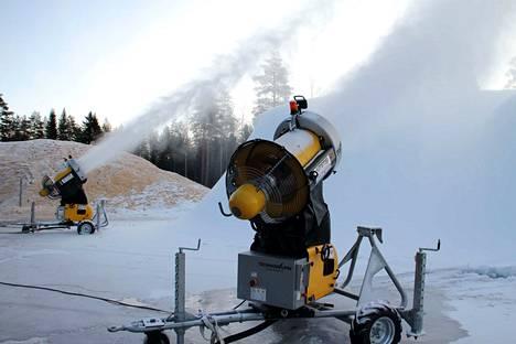 Kaksi lumitykkiä on tehnyt lunta ympäri vuorokauden. Taustalla viime talvena varastoitu lumi vielä sahanpurun alla säilössä.