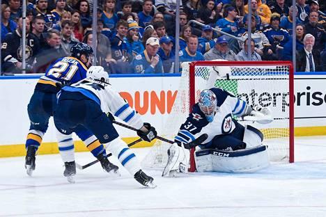 St. Louis Bluesin Tyler Boza ujuttaa kiekon maaliin ohi Winnipeg Jetsin maalivahdin Connor Hellebuyckin ottelun ensimmäisessä erässä.