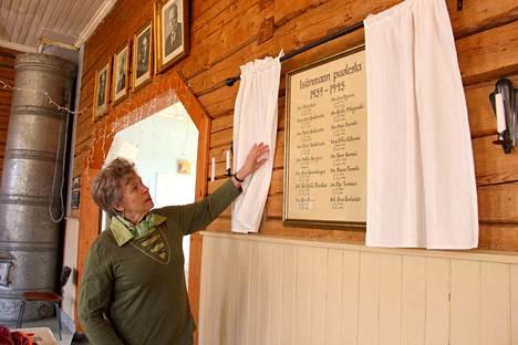 Anja Meura esittelee kylätalon seinälle ripustettua kylän sankarivainajien muistotaulua.