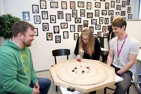 Solitan kammarissa on seinällä työntekijöiden lapsuuskuvia. Tiimipäällikkö Teemu Savon ottaa Henna Gaubusseaun ja Ville Hakolan kanssa erän kanadalaista crokinole-lautapeliä.