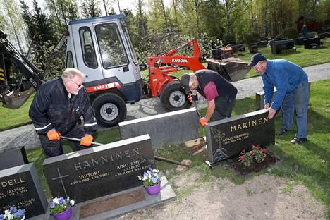 Hannu Mäkinen (oikealla) sai isänsä hautakiven oikaisuun apua suntio Juhani Lehtiseltä ja talkoolaiselta Jussi Ahosmäeltä. Yli 40 vuotta paikallaan seissyt kivi on vaatinut oikaisua vain kerran aiemmin.