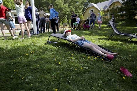 Paavo Kotiranta lepäilee kesäauringossa Kariniemen leirillä. Kohta leikitään kirkonrottaa. Kotiranta odottaa, että pääsisi uimaan.
