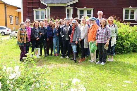Serlachius-maalausleirin osallistujat juhlistivat kymmenettä leiriä yhteiskuvalla Peltolan luomitilan pihapiirissä. Kuvassa edessä keskellä kaikkiin leireihin osallistuneet Helana Karhumäki ja Maarit Ala-Uotila.