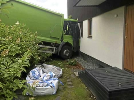 Sekä omakotitalo että jäteauto kärsivät törmäyksessä huomattavia vaurioita.