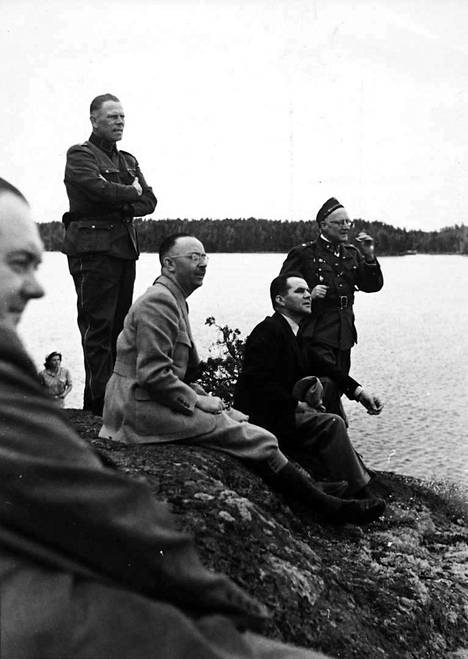 SS-valtakunnanjohtaja Heinrich Himmler ja pääministeri Jukka Rangell istuvat rantakalliolla todennäköisesti Rangellin kesämökillä Luopioisten Kukkiajärvellä elokuussa 1942. Samana päivänä natsijohtaja otti puheenaiheeksi Suomen juutalaiset. Himmlerin henkilääkäri Felix Kersten istuu edessä vasemmalla ja henkivartiostoon kuulunut SS-Obersturmführer Josef Kiermayer seisoo keskellä.