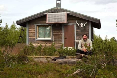 Ami Telilä kotimökkinsä edustalla Inarin Lemmenjoen kultamailla. Aurinkosähköllä saa valoa pirttiin.