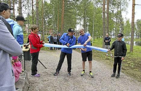 Erkin ja Sepon kierroksen vihkiäisnauhaa leikkaamassa Erkki Pyökkimies ja Seppo Rahkonen. Oikealla naunaa pitelee Kasper Heinonen.