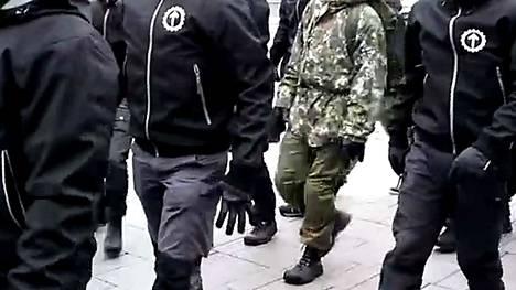 Maavoimien pakkastakissa, maastohousuissa ja karvahatussa Pohjoismaisen vastarintaliikkeen jäsenten kanssa marssinut henkilö oli todennäköisesti asepalvelusta suorittava. Kuvakaappaus videolta.