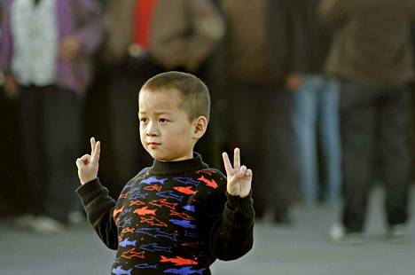 Tiananmenin aukiolla auringonlaskun aikoihin: vanhemmat haluavat ottaa pojastaan kuvan voitonmerkkeineen.