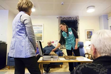 Fysioterapeutti Jenny Turunen soittaa vierailijoiden valitsemia tarinoita ja musiikkia äänimuseon kokoelmista. Vapaaehtoistyöntekijä Lilli Siltanen (vasemmalla) ja Saima Ritalahti kuuntelevat.