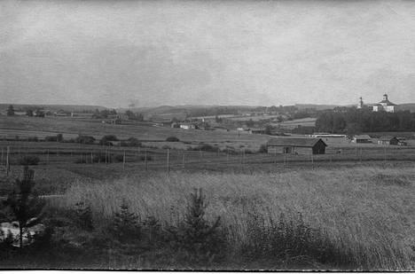 """Jämsäläistä maalaismaisemaa 1917 joen länsipuolelta. Taustalla kirkko ja kellotapuli. Valokuvan maisema on sama kuin Eero Järnelfeltin 1890 maalaamassa taulussa """"Konkolan maisema""""."""
