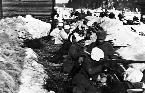 Valkoisten ampumaketju Laviassa. Kuva on otettu Sampakosken taistelun jälkeen Roikan talon ja Pesintien välissä. Kuvan taustalla hiihtää lumipukuisia miehiä.