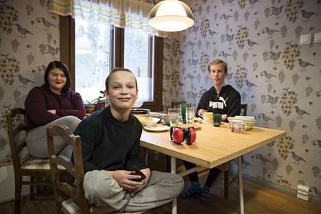 Linnea Päivärinta (vas.) Osmo Vanhasalo ja Verner Söderström (pöydän takana) kertovat omista kiinnostuksen kohteistaan, vanhemmat taustalta välillä täydentävät, jos sanoja ei tunnu löytyvän.