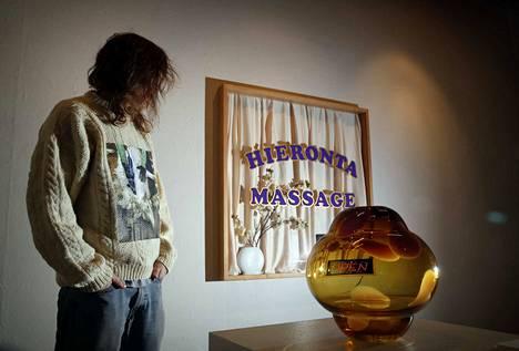 """Simpukkataiteilijalla on yllään yksi taideteoksista, Villapaita, johon on printattu kuva kerittävästä lampaasta. Hän halusi näyttelystään """"Las Vegasin"""", jossa on vähän kaikkea yhteiskunnallisesta ulottuvuudesta huumoriin."""