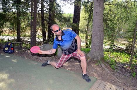 Valkeakoski Disc Golfin puheenjohtaja Ossi Harinen näyttää mallia, miten draiveri toimii Korkeakankaan kakkosväylän tiillä.